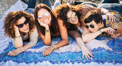 Nice caucasian group of females friends lay down in outdoor leisure activity and have fun together