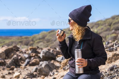 Pretty woman with blonde curly hair and black warm hat enjoying the outdoor activity