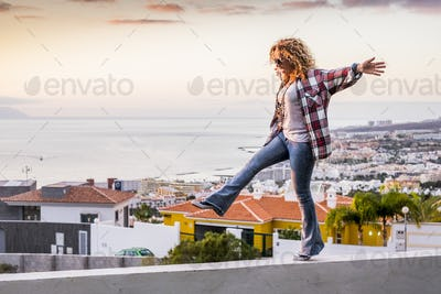 Happy middle age beautiful woman walking in balance having fun like children with city view