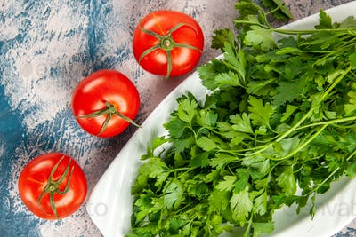 top view fresh greens with tomatoes on a light-blue background ripe salad photo meal color
