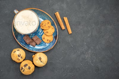 Top view of delicious breakfast with a cup of milk various biscuits and chocolate bars on dark