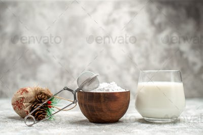 front view wooden bowl with powered sugar and a sieve a glass of milk and xmas toy on grey isolated