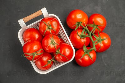 Overhead view of collection of fresh tomatoes inside and outside of a white basket on dark