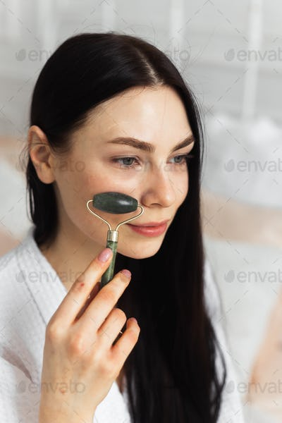Beautiful european woman uses jade roller to massage her face
