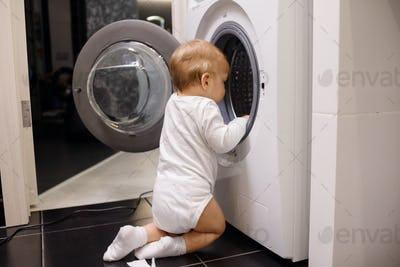 Child climbing into front-loading washing machine. Side view. Lack of parental supervision