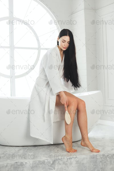 Woman use massage skin brush on her leg for increase circulation and detoxify
