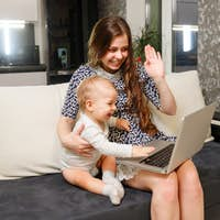 Young woman with kid boy looking at laptop waving hands, make online video call. Social distancing