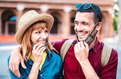 Happy travel couple smiling with open face mask