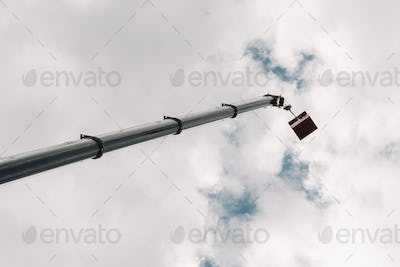 Raised high in the sky cradle of a car crane. The tallest truck crane with a yellow cradle for