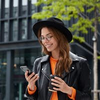 Positive female tourist reads information from travel blog, walks in city street with hot beverage,