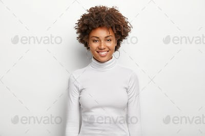 Photo of charismatic lovely woman with curly hair, has fun, toothy smile on face, satisfied after su