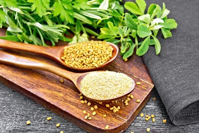 Fenugreek in two spoons with herbs on black board