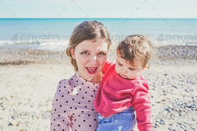 Happy family moment of a young mom enjoying a day on the beach with her baby