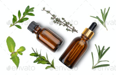 Isolated on white background Dropper bottles with oil and herbs on white table flat lay view