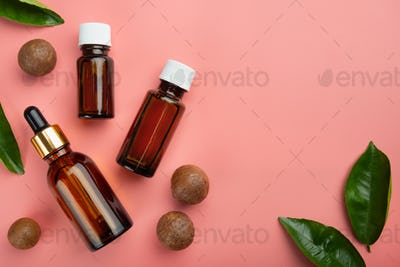 Dropper bottles with macadamia nut essential oil on pink background flat lay design with copy-space