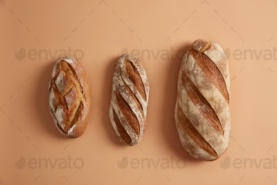 Three tasty loaves of bread arranged on beige background. Gluten free homemade bakery products. Orga
