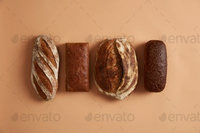 Staple food and healthy nutrition concept. Four types of bread isolated on brown background. Wheat,