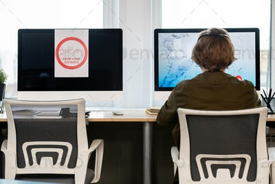 Rear view of male operator of call center sitting in front of computer monitor