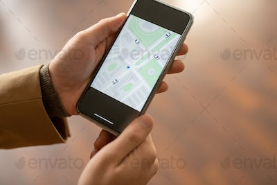 Hands of contemporary young elegant businessman using map in smartphone