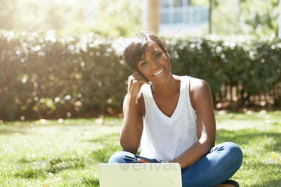 Young romantic black female with pretty smile, sitting on the lawn on a summer day in a thinking pos