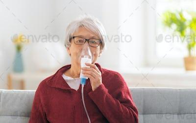 Elderly woman using inhaler for asthma