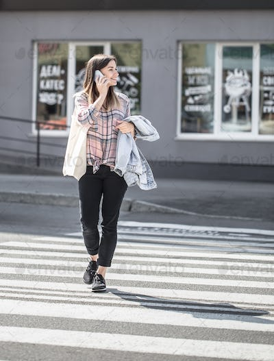Young girl crossing the road at a pedestrian crossing with eco bag and phone