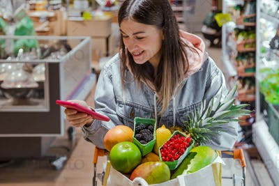 A young woman buys groceries in a supermarket with a phone in her hands.