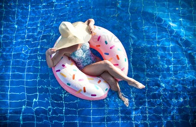A woman in a hat relaxes on an inflatable circle in the pool.