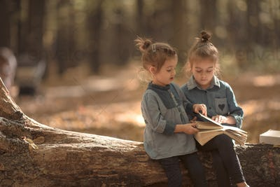 two little girls reading books in the woods.