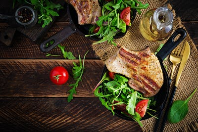 Juicy grilled pork steak with herbs on bone on wooden background. Top view, overhead, flat lay