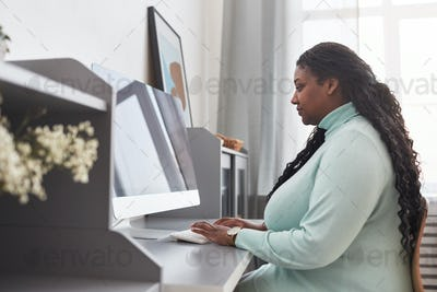 Overweight African American Woman Working from Home Side View