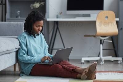 Real African American Woman Using Laptop on Floor