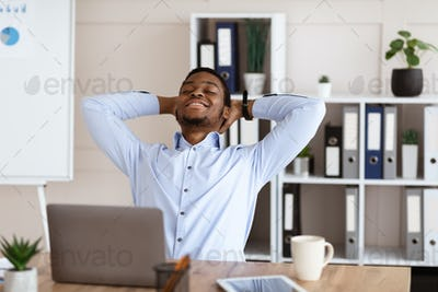 Joyful african american employee resting on his chair