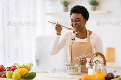 Happy African American Woman Cooking Tasting Dinner In Kitchen Indoor