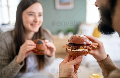 Unrecognizable young couple in love eating hamburgers indoors at home.