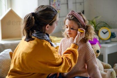 Sisters indoors at home, applying mascara. Lockdown concept.