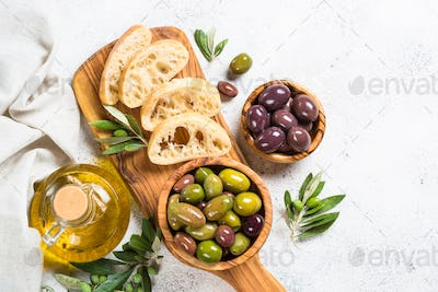 Olives, ciabatta and olive oil on white background.