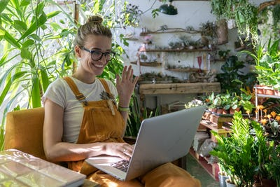 Woman gardener using laptop smiling talking in video chat say hello her friend sitting in greenhouse