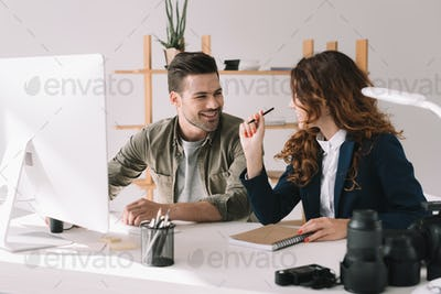 male and female photographers working together in modern office