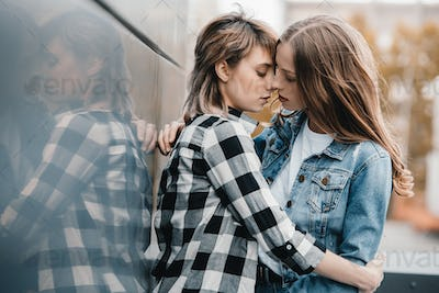 Beautiful young lesbian couple hugging and kissing outdoors