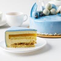 cake on chopping board with tea cups and slice on plate isolated on white