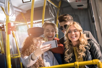 cheerful young friends taking selfie with smartphone in bus