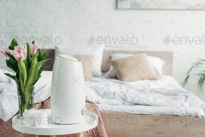white ultrasonic purifier, tulips and candles on table in bedroom