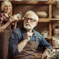 Senior potter sitting at table and thinking with senior woman at workshop