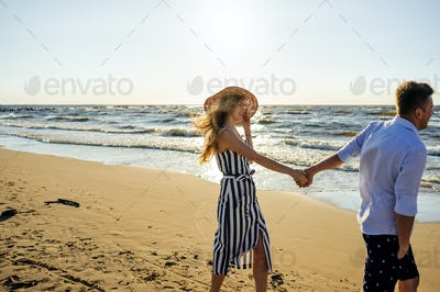 side view of young smiling couple in love holding hands on sandy beach in Riga, Latvia