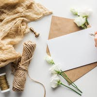 cropped view of woman writing in card with ink pen near eustoma, cloth, envelope and wrapped gift on