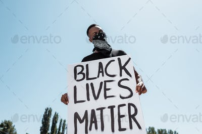 low angle view of african american man with scarf on face holding placard with black lives matter