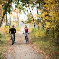 Adult couple cycling outdoors in beautiful autumn park