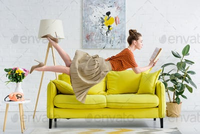 elegant young woman levitating in air while reading book