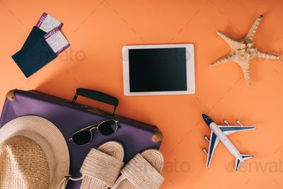 top view of summer accessories on travel bag, plane model, digital tablet and passports with tickets